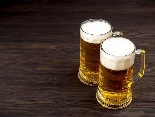 Copo de cerveja na mesa de madeira com copyspace Foto Premium