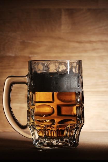 Copo de cerveja sobre a superfície de madeira Foto gratuita