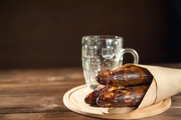 Copo de cerveja vazio e close-up de peixe defumado quente. caneca e peixe vazios de cerveja em um espaço escuro do fundo e da cópia. Foto Premium