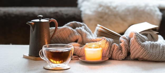 Copo de chá, bule, vela e livro com elemento de malha. o conceito de conforto e aconchego do lar. Foto gratuita