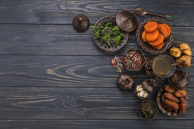 Copo de chá com diferentes frutas secas na mesa Foto gratuita