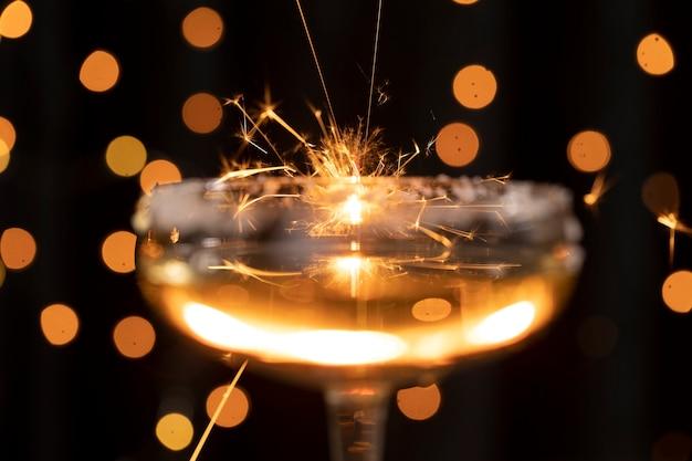Copo de close-up com champanhe e luzes douradas Foto gratuita
