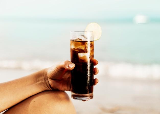 Copo de coca-cola com gelo na mão na praia Foto gratuita