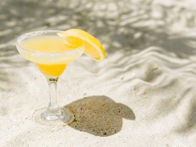 Copo de cocktail amarelo com fatia de limão colocado na areia Foto gratuita
