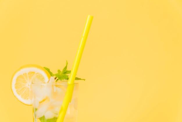 Copo de cocktail com palha e limão no fundo amarelo Foto gratuita