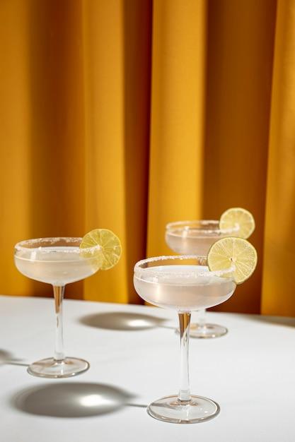 Copo de coquetel margarita decore com limão na mesa contra a cortina amarela Foto gratuita