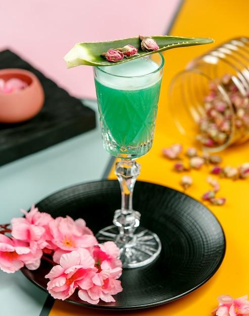 Copo de coquetel verde decorado com licença de aloe e botões de rosa secos Foto gratuita