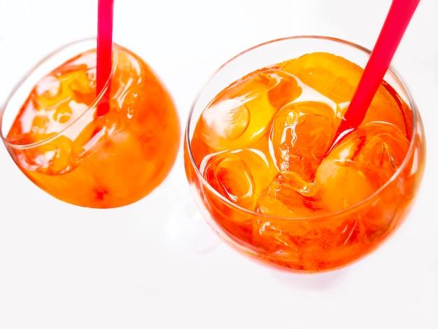 Copo de espumante aperol spritz cocktails com palhas isolado no branco Foto Premium