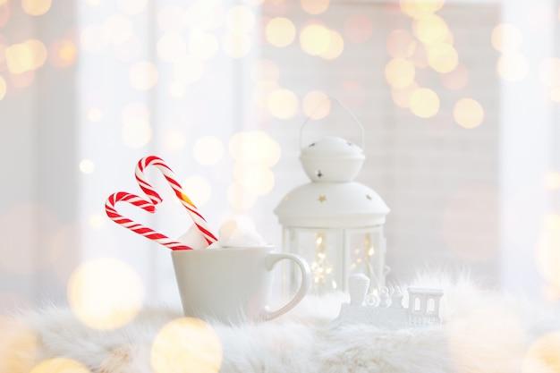 Copo de inverno de bebida quente com um bastão de doces em fundo branco de madeira Foto gratuita