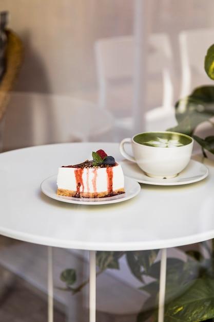 Copo de latte de chá verde matcha e cheesecake com molho de frutas e hortelã verde na mesa branca Foto gratuita
