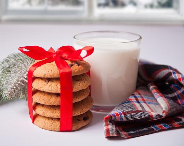 Copo de leite, biscoitos e ramo de pinheiro Foto Premium