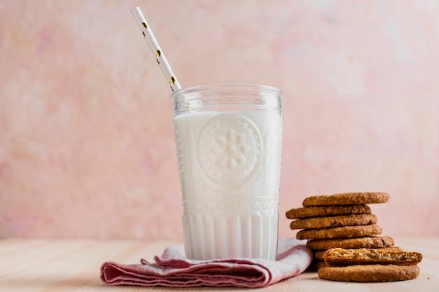 Copo de leite com vista frontal com palha e biscoitos Foto gratuita
