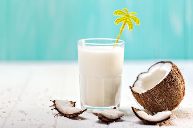 Copo de leite de coco na mesa de madeira branca. foco seletivo Foto Premium