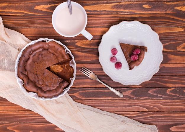 Copo de leite; fatia de bolo e framboesa na placa cerâmica branca sobre a superfície de madeira Foto gratuita