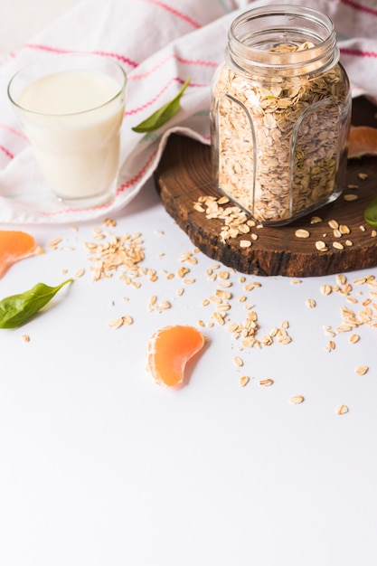 Copo de leite; folhas de manjericão; aveia; fatias de laranja e guardanapo no fundo branco Foto gratuita