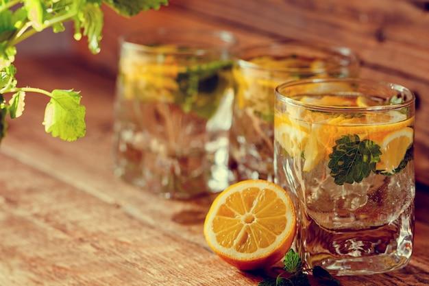 Copo de limonada com limão e hortelã no fundo de madeira Foto Premium