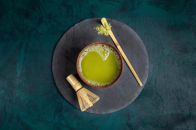 Copo de madeira com chá verde do matcha na placa redonda do serviço do xisto no fundo esmeralda. vista do topo. Foto Premium