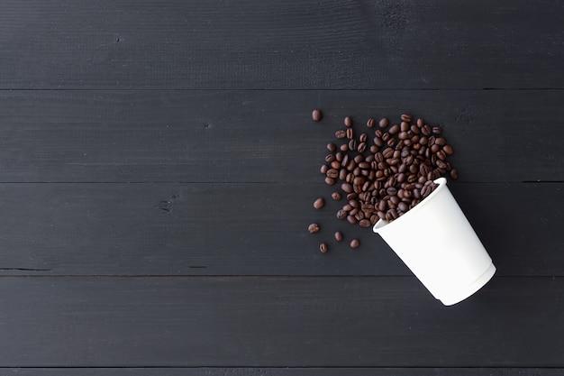 Copo de papel branco e feijões de café no fundo de madeira velho. vista do topo Foto Premium