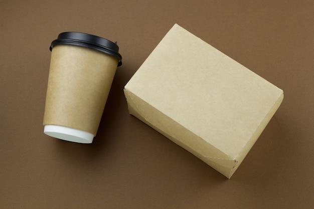 Copo de papel descartável de vista superior com tampa plástica e caixa de papelão mock-se no fundo marrom Foto Premium