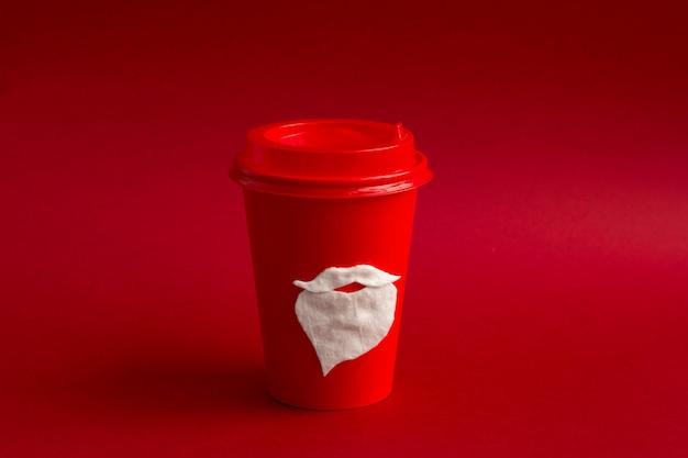 Copo de papel descartável vermelho para bebidas para viagem com bigode de algodão e barba do papai noel Foto Premium
