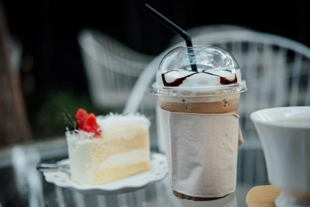 Copo de plástico de café gelado com bolo na mesa na loja de café Foto gratuita
