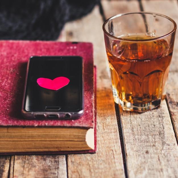 Copo de ponche de laranja, livro, smartphone e coração Foto Premium