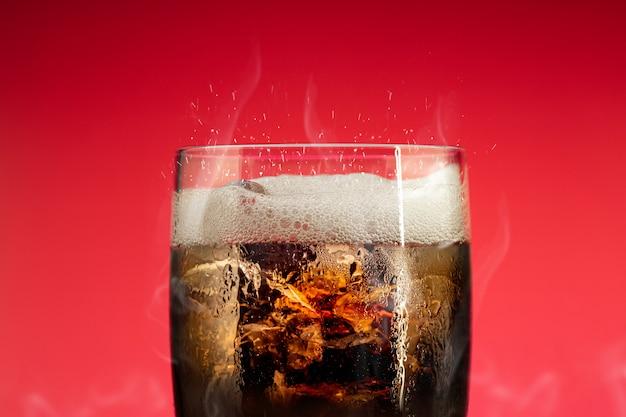 Copo de refrigerante com respingo de gelo. cola de vidro com refresco de verão. Foto Premium