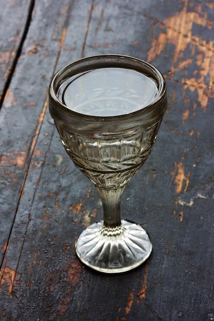 Copo de shot vintage com vodka em uma velha mesa de madeira preta Foto Premium