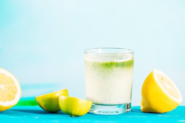 Copo de smoothie verde saudável e citrinos em fatias Foto gratuita