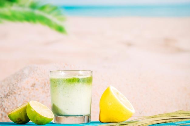 Copo de suco batido fresco e fatias de frutas cítricas Foto gratuita