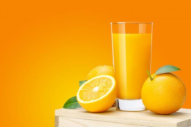 Copo de suco de laranja fresco na caixa de madeira, suco de laranja de frutas frescas em vidro com grupo sobre fundo de cor laranja com espaço de cópia para o seu texto. Foto Premium
