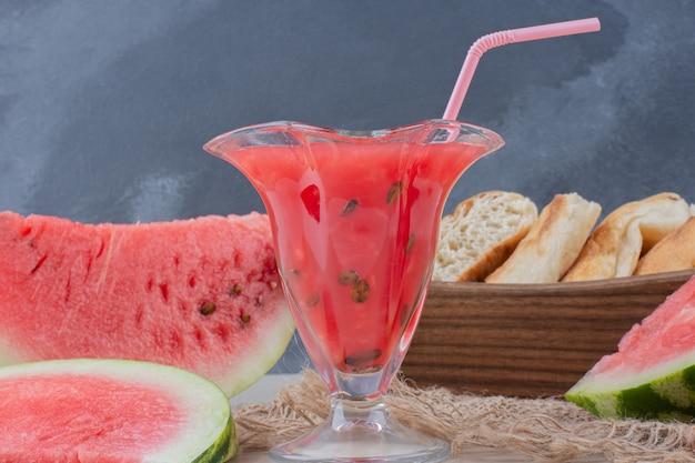 Copo de suco de melancia e cesta de pão na mesa branca. Foto gratuita