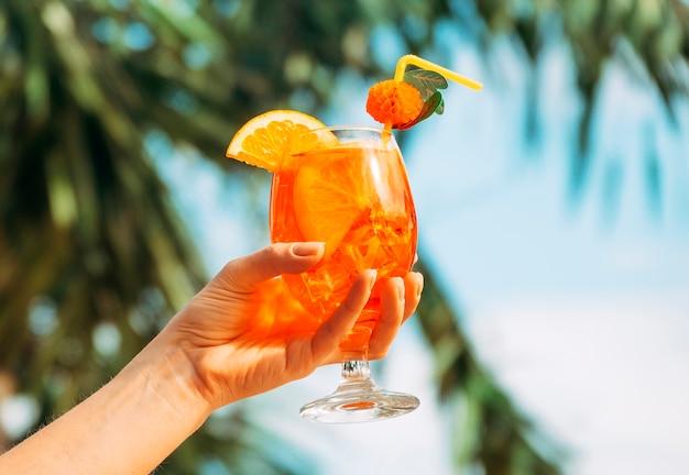 Copo de suco fresco de laranja brilhante na mão Foto gratuita