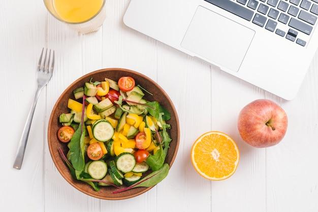 Copo de suco; laranja ctrica; maçã e salada mista de legumes com garfo e laptop na mesa de madeira branca Foto gratuita
