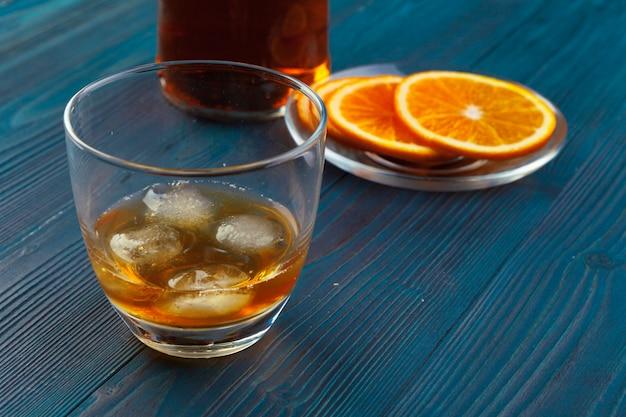 Copo de uísque com frutas laranja cortadas no escuro de madeira Foto Premium