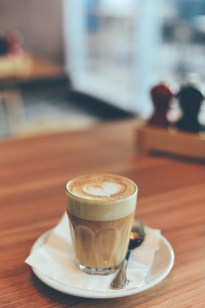 Copo de vidro com café e uma colher de chá Foto gratuita