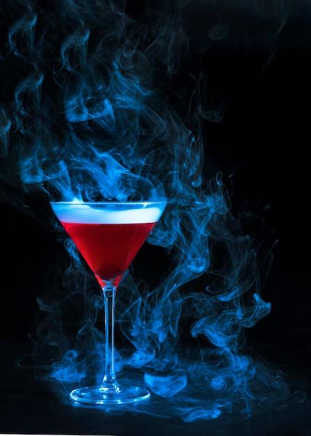Copo de vinho com bebida vermelha e fumaça Foto gratuita