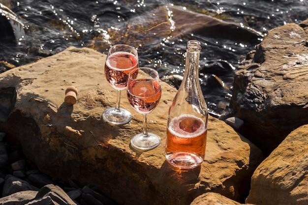 Copo de vinho de alta vista e garrafa nas rochas do oceano Foto Premium
