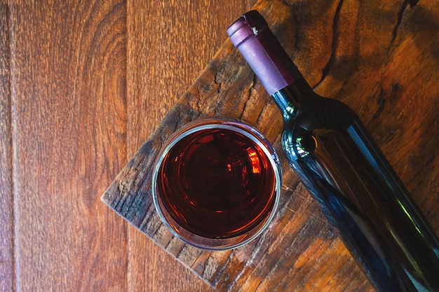Copo de vinho e garrafa de vinho na mesa de madeira Foto Premium