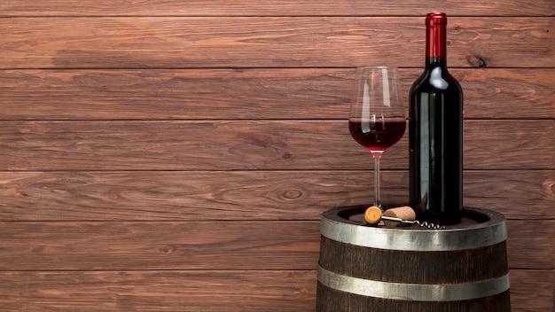 Copo de vinho e garrafa em um barril Foto Premium