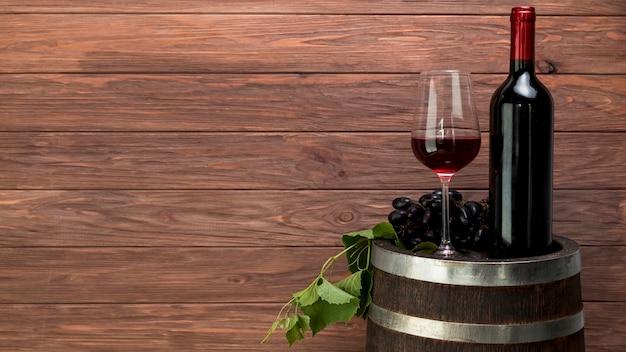 Copo de vinho e garrafa em um barril Foto gratuita