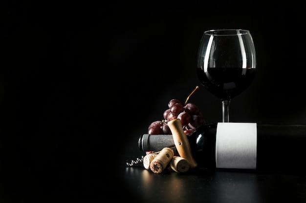 Copo de vinho e garrafa perto de saca-rolhas e uva Foto gratuita
