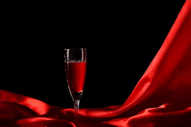 Copo de vinho na seda vermelha com fundo escuro Foto Premium