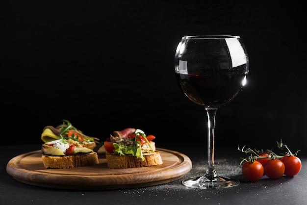 Copo de vinho perto de sandes abertas Foto gratuita