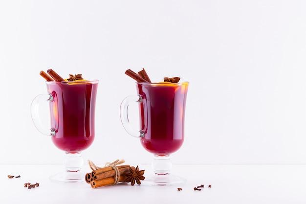 Copo de vinho quente quente com especiarias em fundo branco Foto Premium