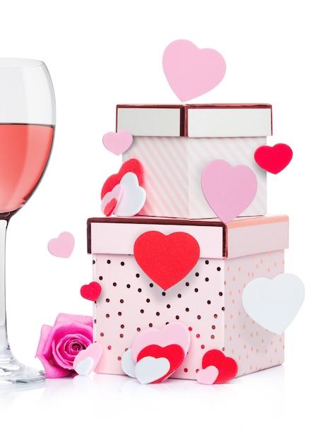 Copo de vinho rosa com coração e caixa de presente rosa e rosa para dia dos namorados em fundo branco com coração voador Foto Premium