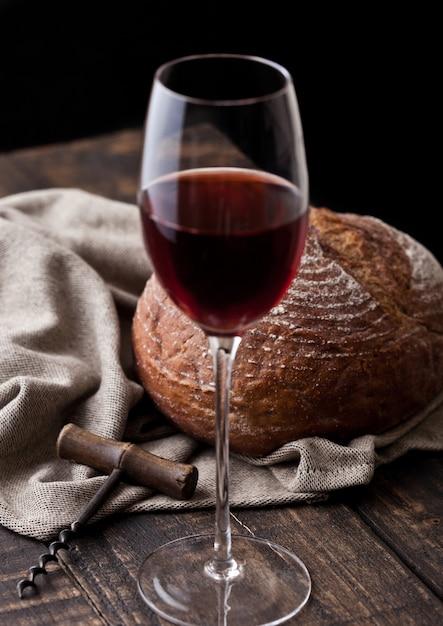 Copo de vinho tinto com pão fresco com saca-rolhas retrô na cozinha na mesa de madeira Foto Premium