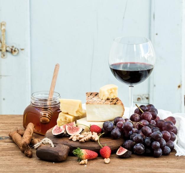 Copo de vinho tinto, tábua de queijos, uvas, figo, morangos, mel e pão gruda na mesa de madeira rústica, azul Foto Premium