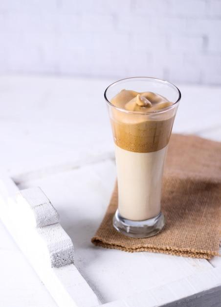 Copo de vitamina de caramelo em uma peça de roupa marrom ao lado de uma superfície branca Foto gratuita