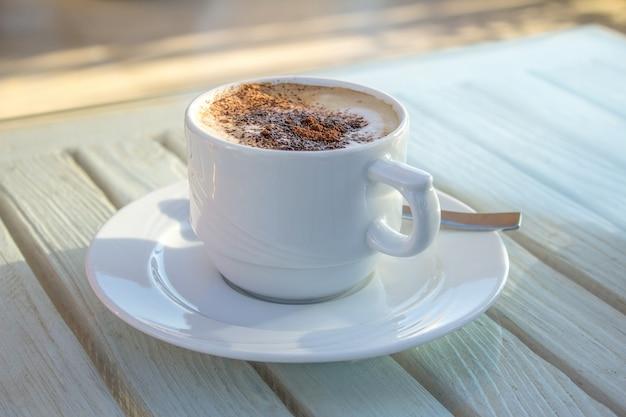 Copo do cappuccino com arte do latte do cardamomo na tabela branca de madeira. Foto Premium